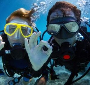 underwater shoot of a young couple diving with scuba in a tropical sea and showing ok signal shutterstock 127605290